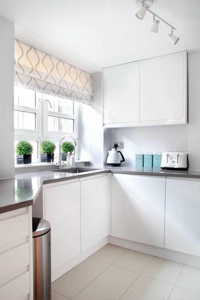 A cozinha branca e clean apostou em uma persiana romana branca com estampa neutra e suave