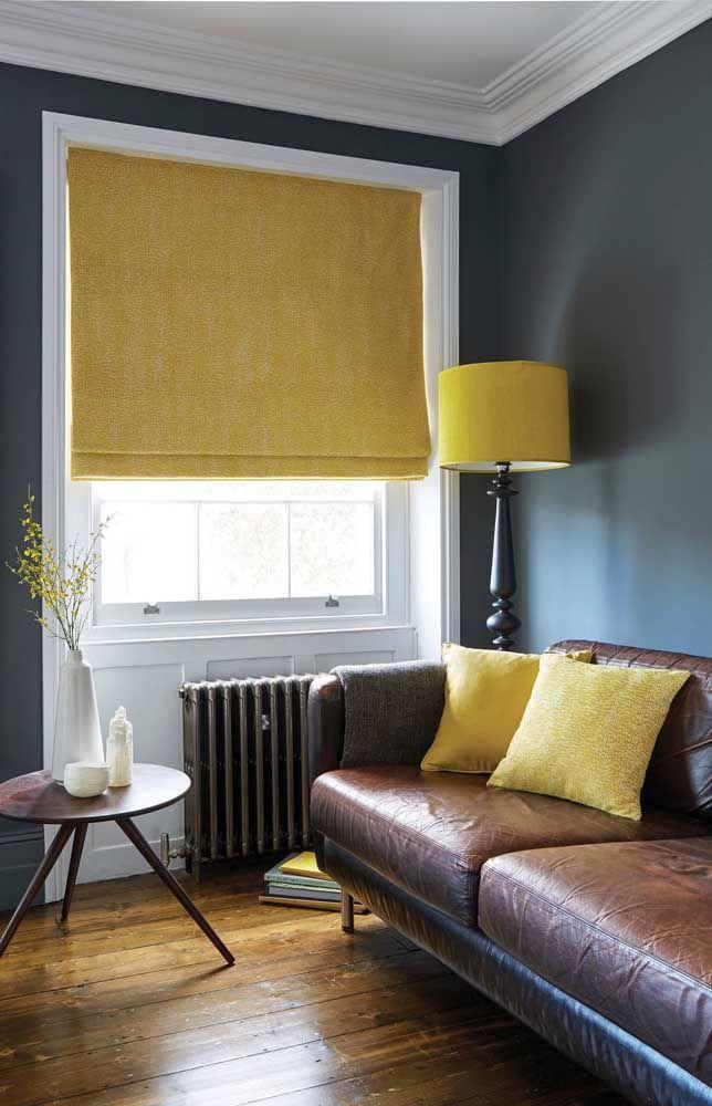 Sala de estar marcada pelo contraste entre o azul da parede e o amarelo da persiana romana; uma proposta original e cheia de estilo