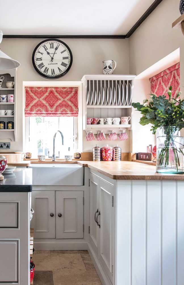 A cozinha de estilo clássico apostou em uma dupla de pequenas persianas romanas estampadas e de cor vibrante