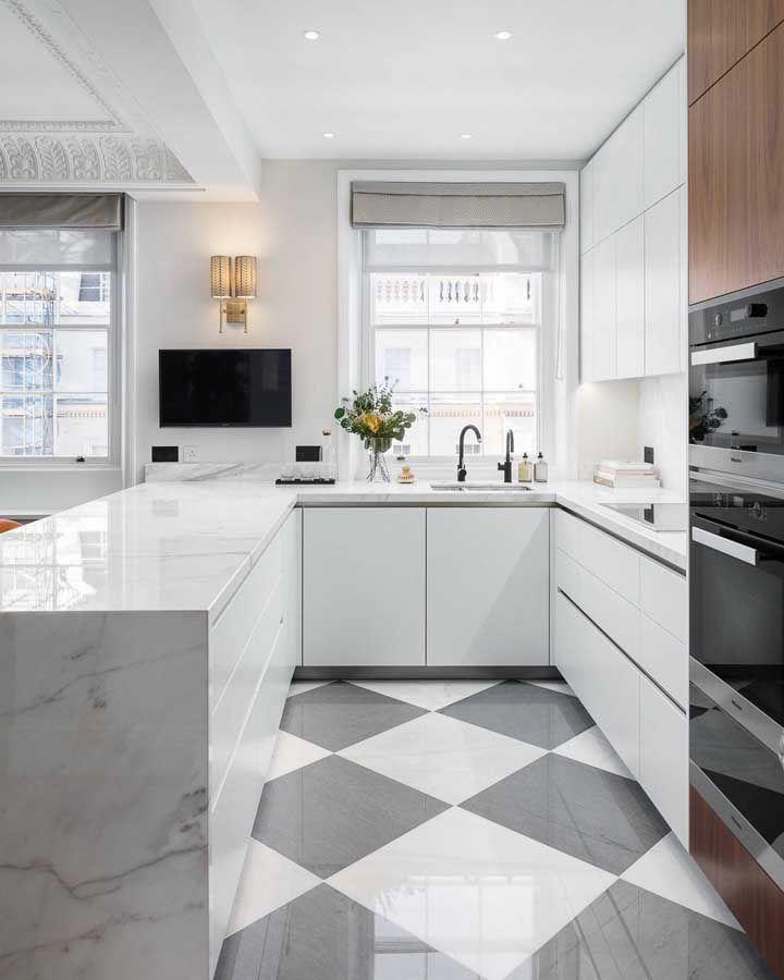 A persiana romana cinza dessa cozinha acompanha a neutralidade do ambiente e ainda se harmoniza com o piso