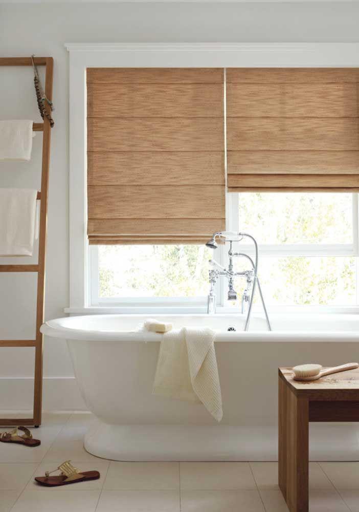Os elementos em madeira desse banheiro se ligam diretamente ao tom da persiana romana