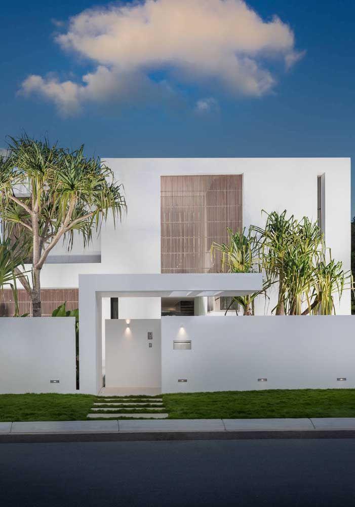 Essa casa quadrada toda branca ganhou um belo contraste com as palmeiras em tom de verde vivo