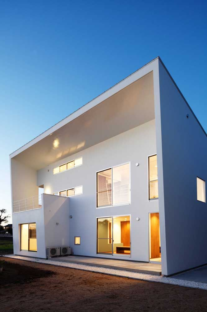 Branca, quadrada e com um projeto de iluminação que valoriza a fachada durante a noite