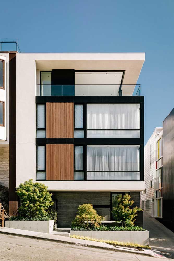 Branco, preto e madeira na fachada da casa quadrada; um típico exemplo de projeto moderno e minimalista