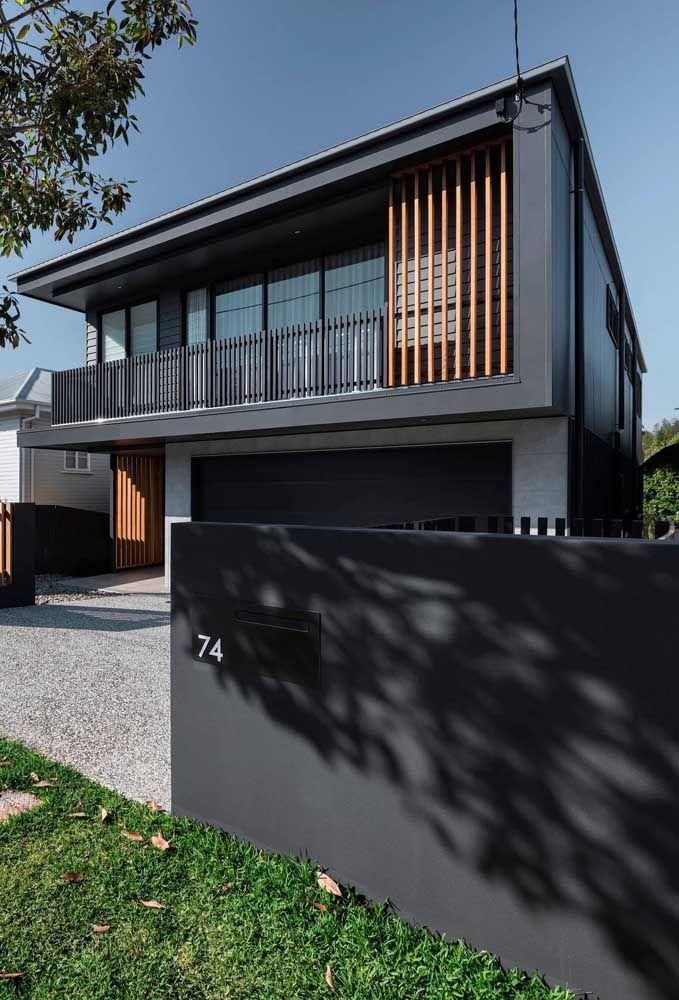 A elegância da cor preta e da madeira emprestada a essa fachada de casa quadrada