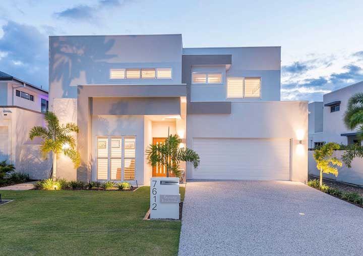 As luzes na entrada da casa formam um jogo de sombras capaz de mudar a cor da fachada, indo do branco para o cinza