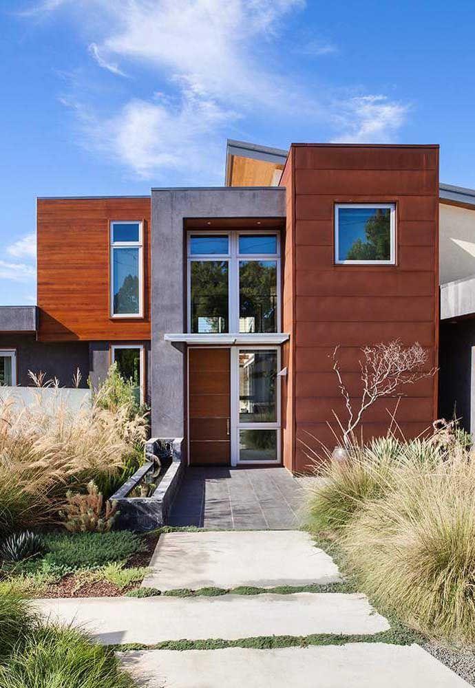 Acabamento é tudo quando o assunto é fachada de casas quadradas: essa aqui, por exemplo, apostou na combinação entre cimento queimado, aço corten e madeira