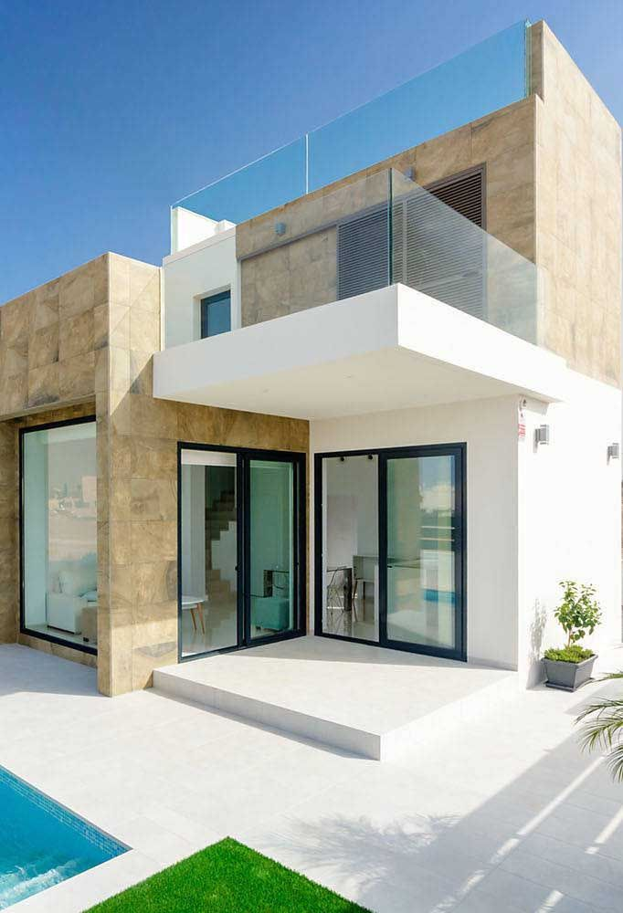 Projeto de casa quadrada com piscina; destaque para a combinação entre o vidro e o revestimento de pedras