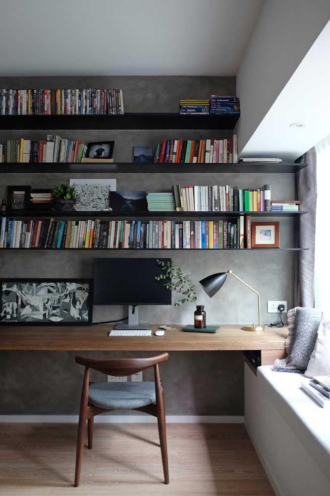 O home office é um lugar perfeito para os livros; destaque para a cor preta das prateleiras em contraste com a parede de cimento queimado