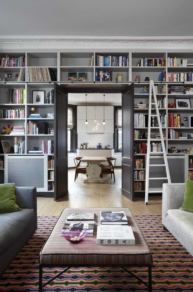 Essa sala de estar ganhou uma parede inteira recoberta de livros; a escada auxilia na busca pelos títulos