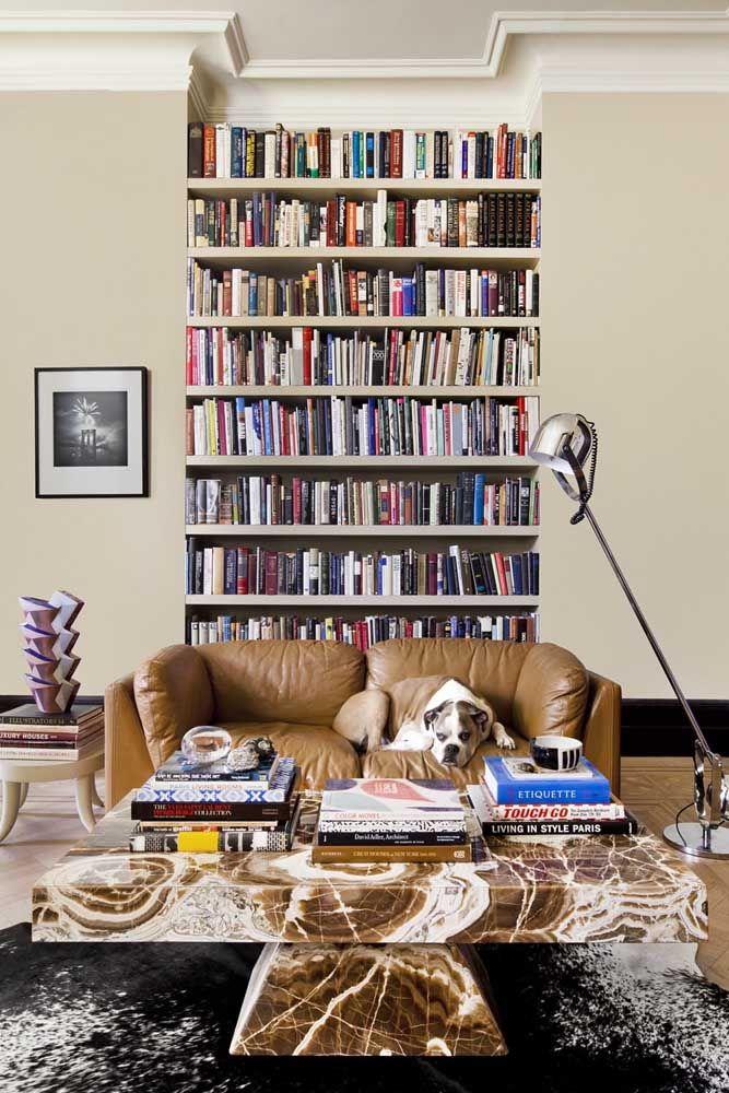 A faixa de livros criada na parede cria uma sensação de amplitude vertical na sala