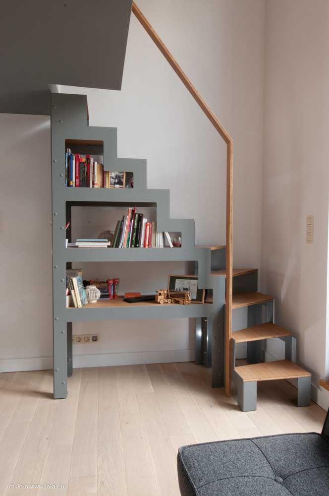 O espaço embaixo da escada foi aproveitado de um jeito divertido para as prateleiras de livros