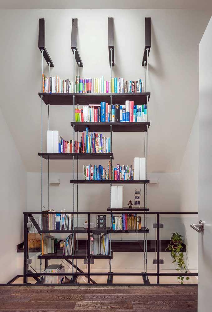 Um modelo de estante para livros moderna e que atravessa o pé direito duplo da casa