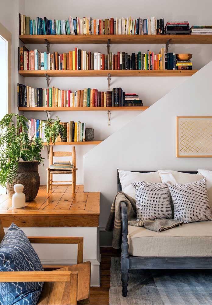 Prateleiras para livros na mesma tonalidade de madeira que predomina no restante do ambiente