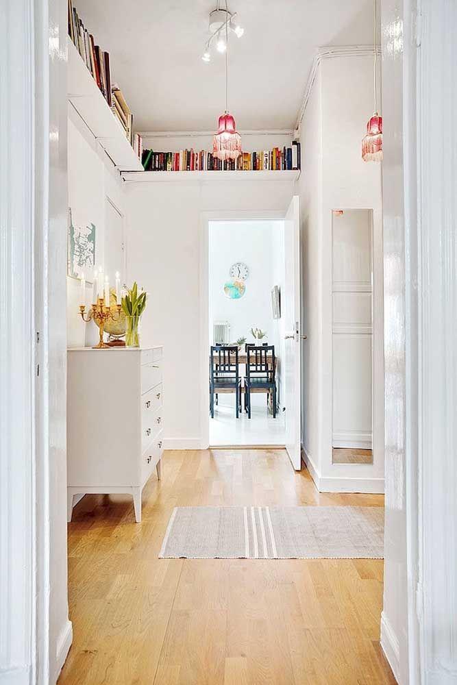 Para o alto: aqui, os livros foram posicionados acima da altura da porta em uma prateleira em L