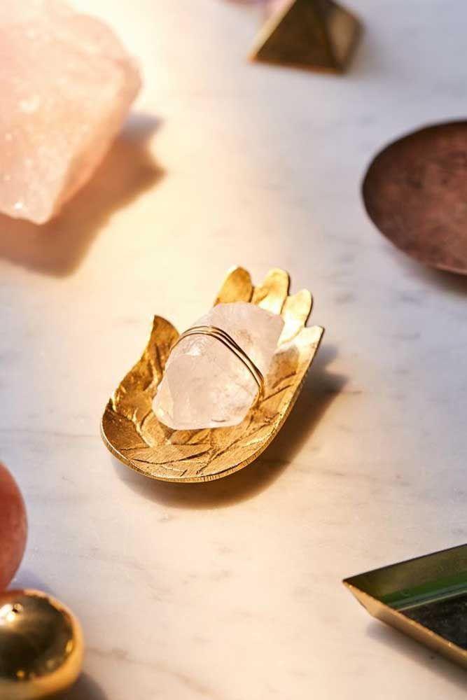 A mão dourada acolhe com ternura o pequeno cristal de quartzo