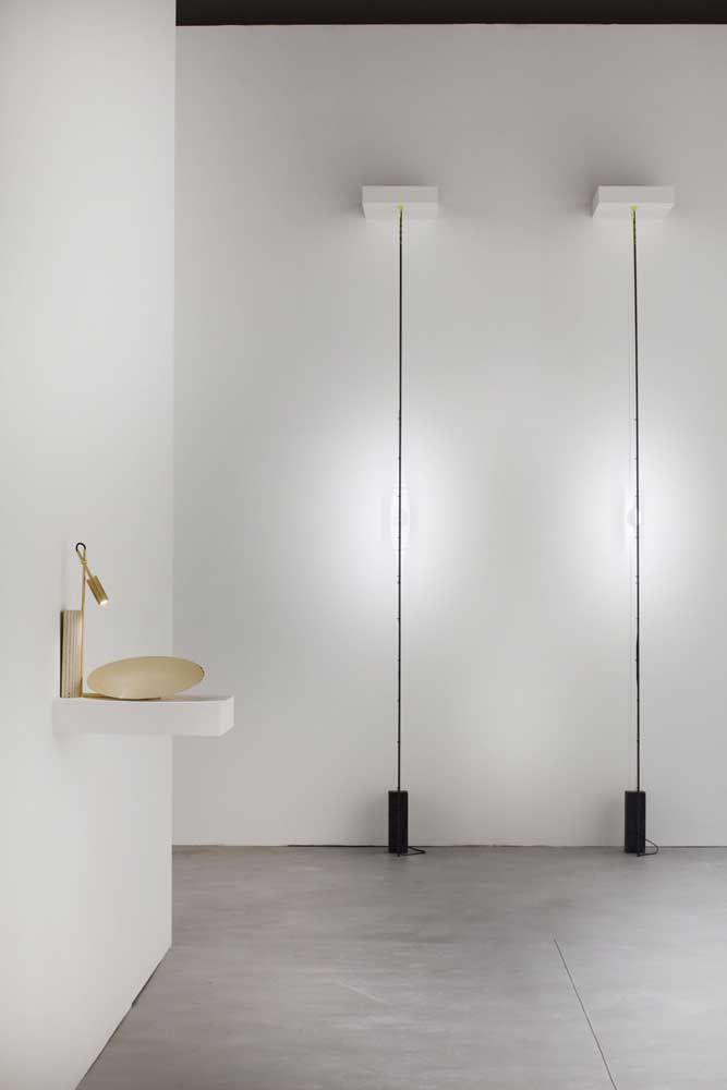 A luminária vertical que vai até o chão cria o ponto luminoso no centro da parede; uma peça de design criativo e inusitado