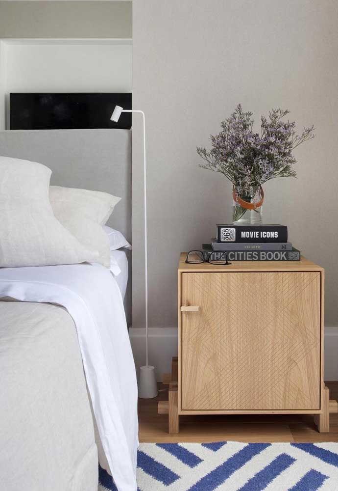 Discreta, ao lado da cama, a luminária cumpre sua dupla função