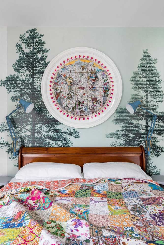 Pinheiros na cabeceira da cama; entre eles um quadro que esbanja cores e texturas