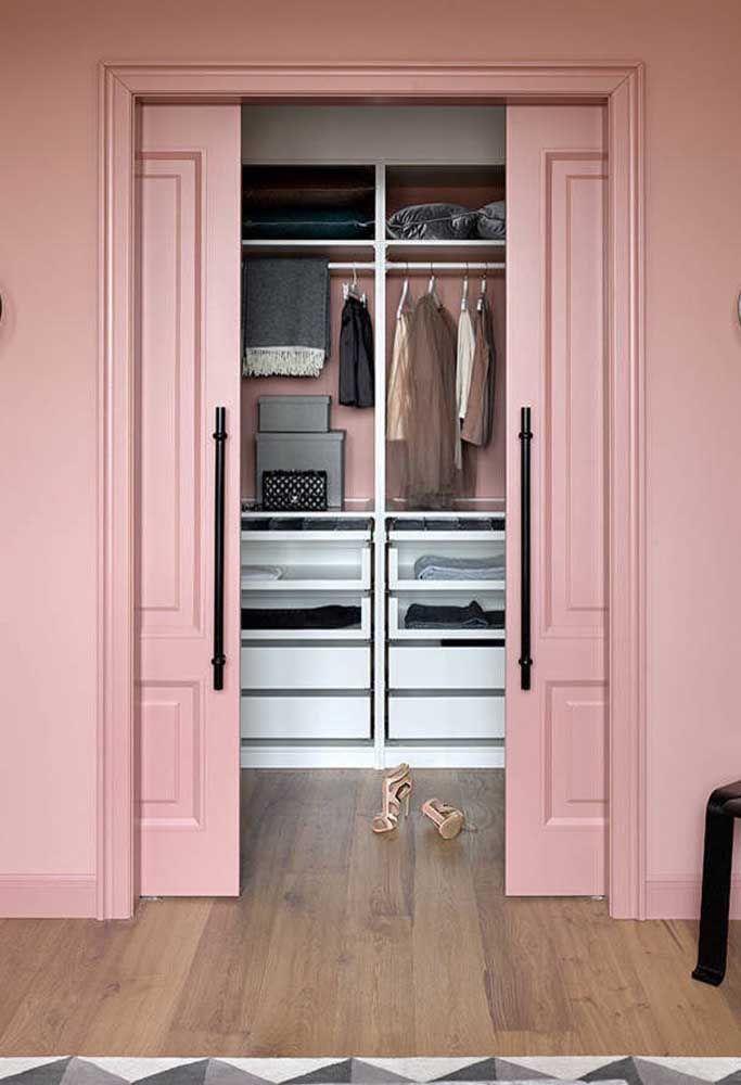 A porta de correr rosa com boisseries é um mix entre o clássico e o moderno