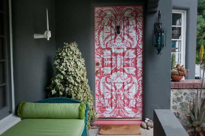 A porta de entrada tem um peso importante no design da casa, pensando nisso, a proposta aqui foi texturizar a porta com um fundo rosa e desenhos brancos