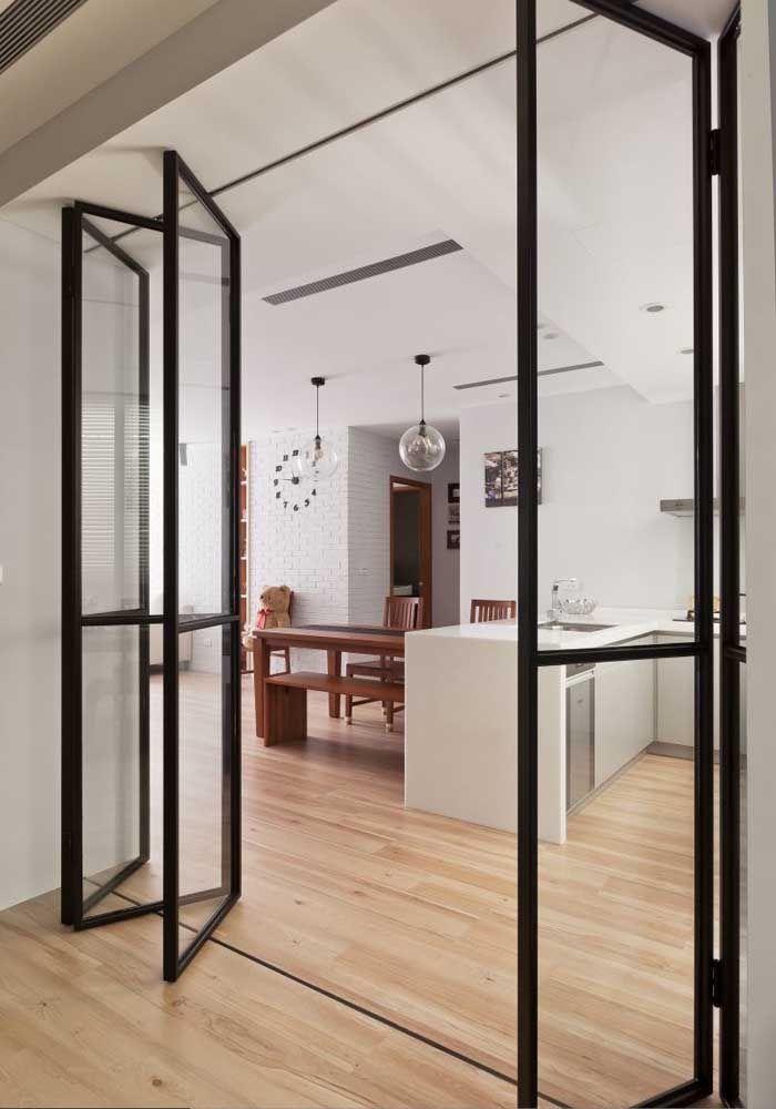 O ambiente clean e moderno conta com uma elegante porta de vidro com estrutura preta para delimitar os espaços
