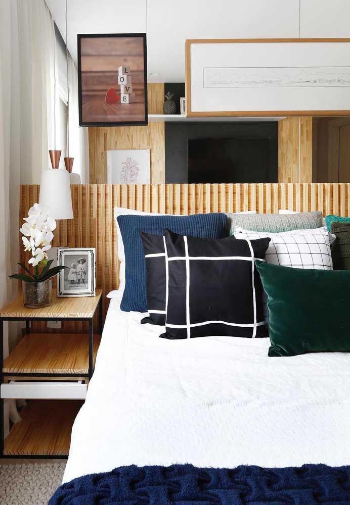 Ripas de madeira formando a cabeceira da cama de casal
