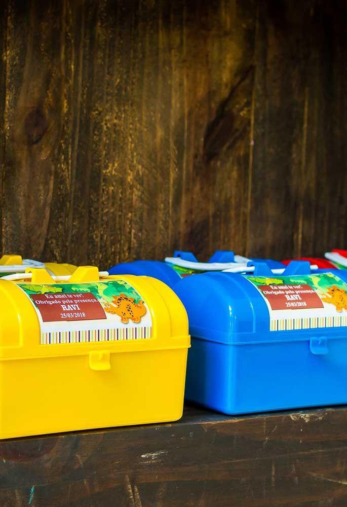 Compre algumas maletas de plástico e cole adesivos personalizados com o tema dinossauros. Dentro encha de guloseimas.