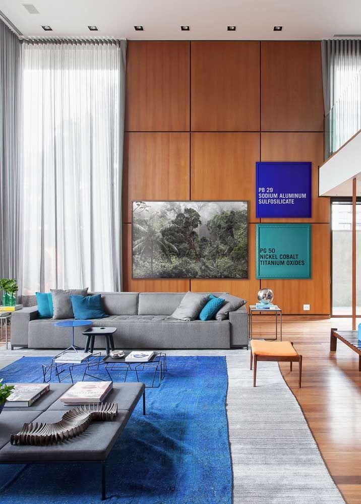 Quadros e longas cortinas para essa sala de estar com pé-direito duplo