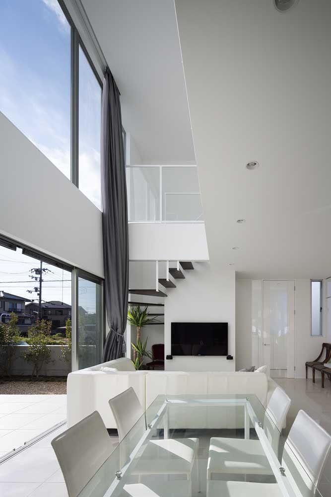 Ambientes integrados, mezanino e claridade para essa casa com pé direito alto em estilo clean