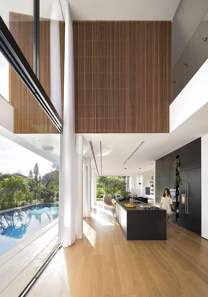 Nessa inspiração, a casa com pé-direito duplo ganhou um lindo painel em madeira para revestir parte do mezanino