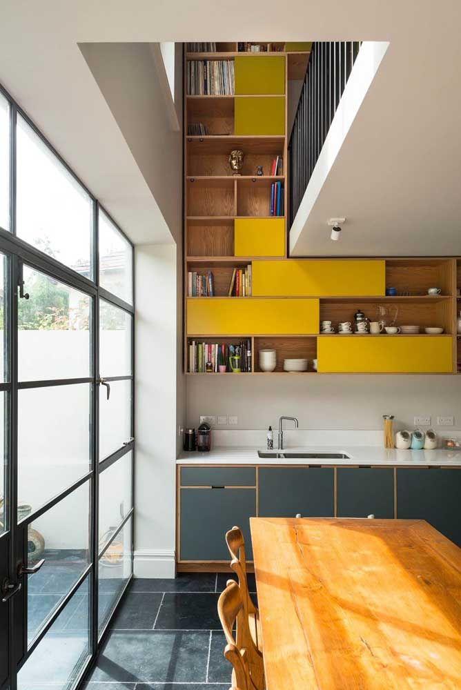 A estante amarela explorou bem o espaço disponível proporcionado pelo pé-direito duplo da cozinha
