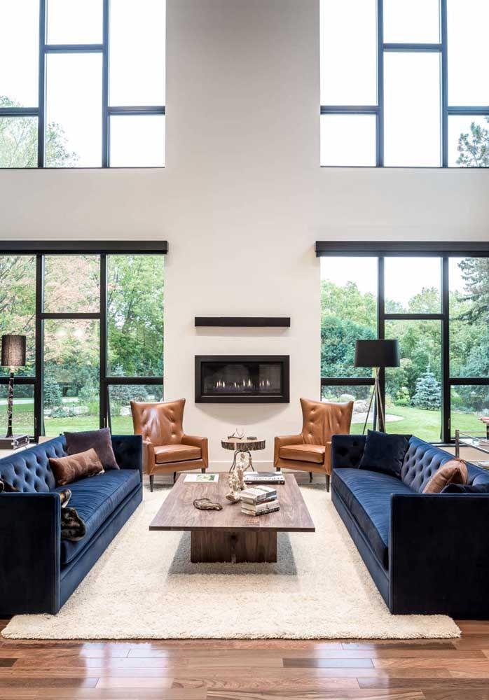A sala de estar ficou aconchegante com a lareira em conjunto com o pé-direito duplo