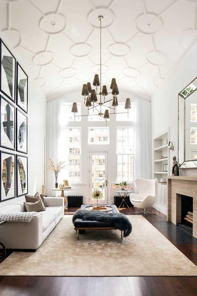 Salas de estar com pé-direito duplo podem contar com lustres chiquérrimos e um teto feito com placas de gesso 3D