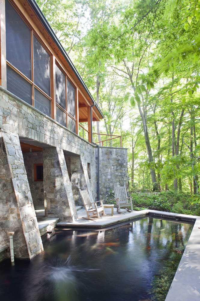 Feito em alvenaria, o lago artificial com carpas encanta o exterior da casa e proporciona uma vista incrível