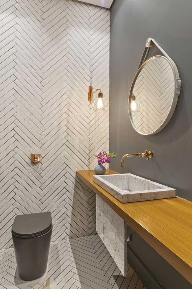 Vaso sanitário cinza de design moderno com válvula de descarga na parede; repare que a cor dourada da válvula acompanhe os outros metais