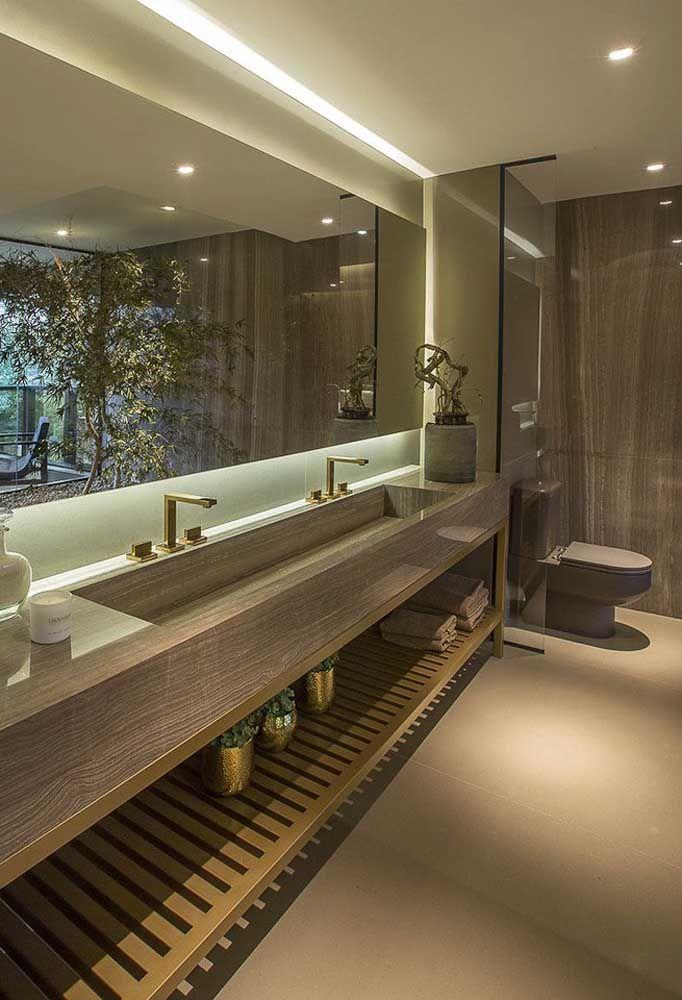 Nesse banheiro, o vaso sanitário marrom ganhou uma área reservada; destaque para a cor do vaso que se harmoniza com os tons de madeira