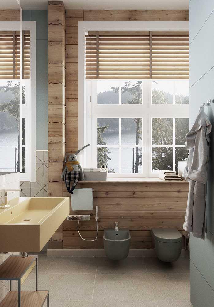 Junto a parede de madeira, o vaso sanitário e o bidê formam uma dupla perfeita