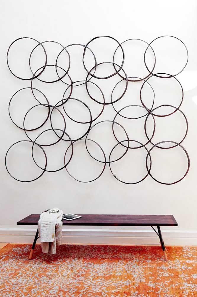 Os círculos de ferro foram entrelaçados para compor a escultura de parede; proposta simples, mas cheia de estilo