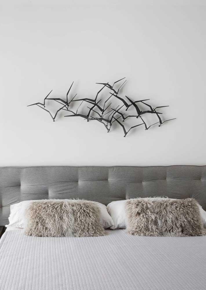 Os pequenos pássaros feitos em ferro viraram escultura de parede para valorizar o quarto do casal