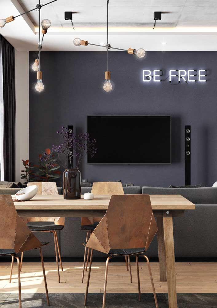 Sala dois ambientes decorada em estilo moderno e despojado; o sofá demarca o limite entre a sala de jantar e a sala de estar