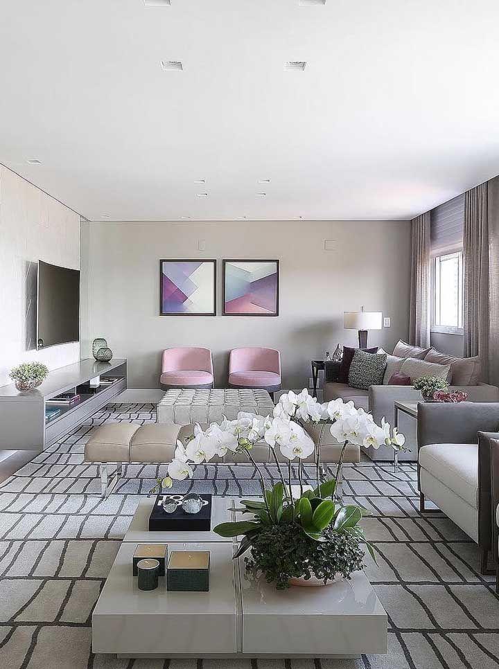 Ampla, essa sala dois ambientes ganhou continuidade visual com o uso de um único tapete; repare que o tom de cinza predomina em ambos espaços