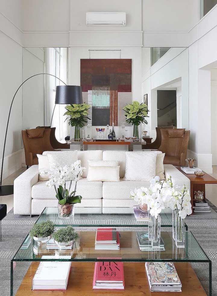 Essa sala dois ambientes ganhou amplitude visual com o uso da faixa de espelhos na parede aos fundos