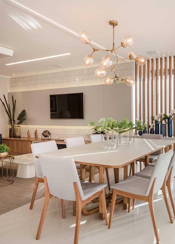 Os detalhes fazem a diferença nessa sala dois ambientes, entre eles a parede 3D com luz atrás da TV, o lustre sobre a mesa de jantar e o painel ripado de madeira