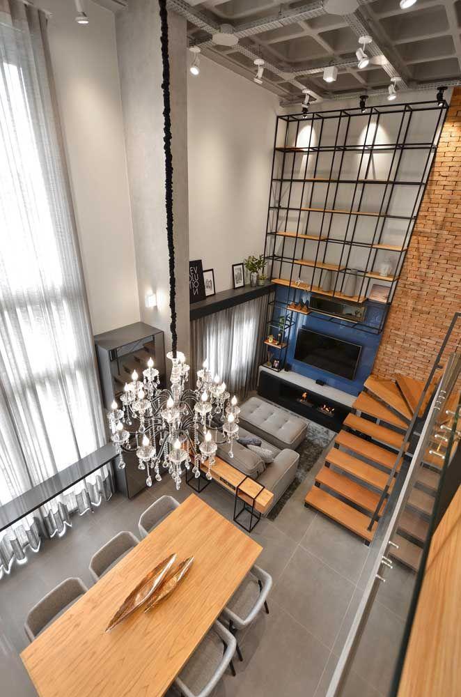 O destaque dessa sala dois ambientes, além é claro do pé direito duplo, vai para o lustre clássico que se estende até alcançar a mesa de jantar