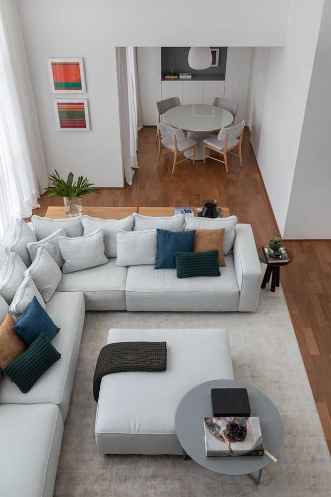 O sofá de canto otimiza o espaço da sala dois ambientes e ainda ajuda a demarcar cada área