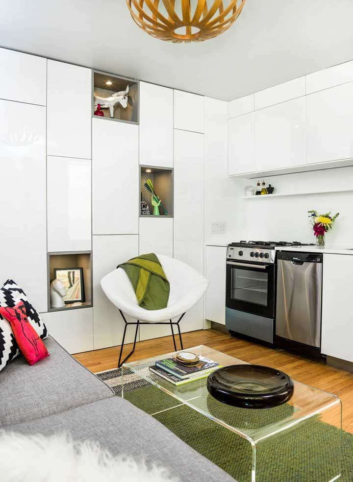 Esse pequeno espaço contempla com muito charme cozinha e sala de estar; repare que os armários brancos na parede organizam a despensa e não pesam no visual