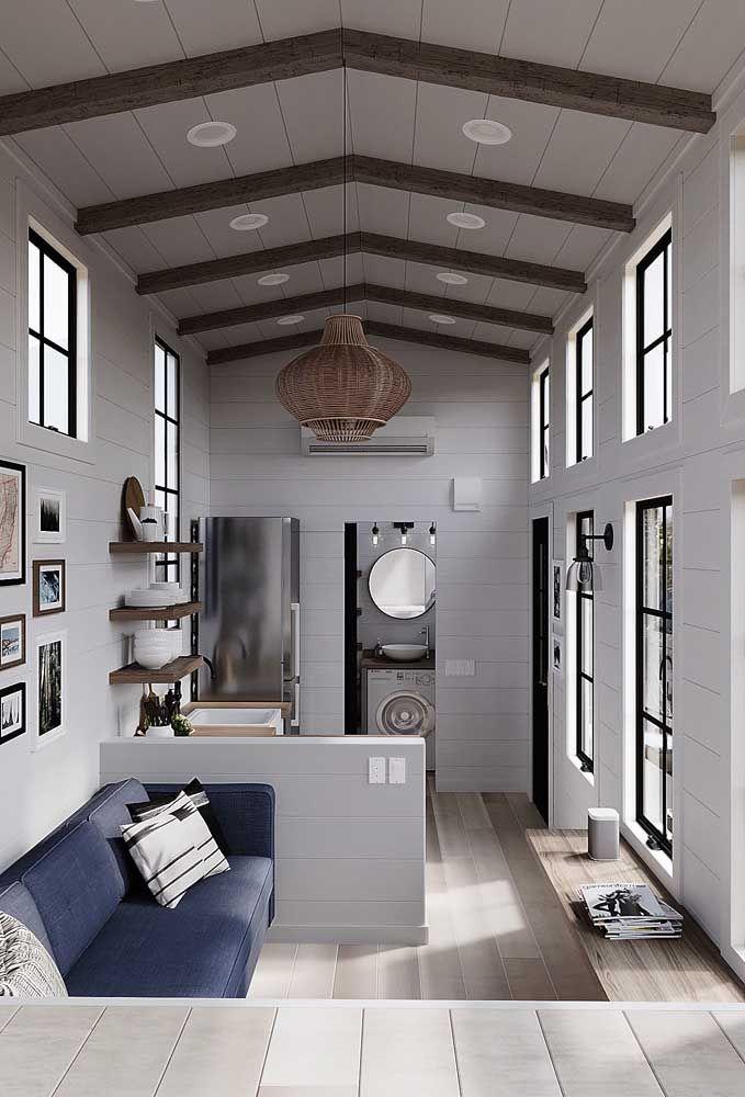O pé direito alto dessa mini casa permitiu o uso de diversas janelas e até mesmo de um lustre