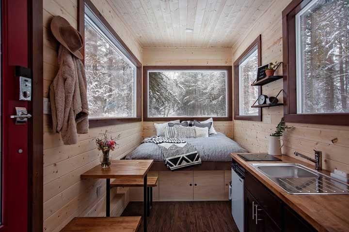 Armário sob a cama, mesinha lateral, cabideiro na parede e prateleiras: tudo pensado para otimizar o espaço dentro da mini casa