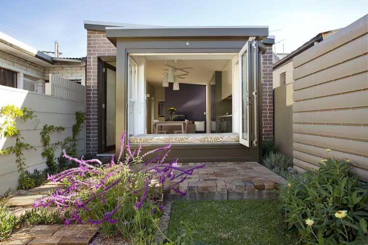 A porta de vidro de correr garante o acesso para a área externa da mini casa